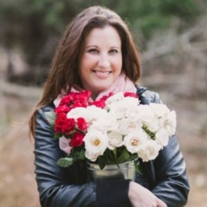 Kristy Tracey outdoors holding floral bouquet
